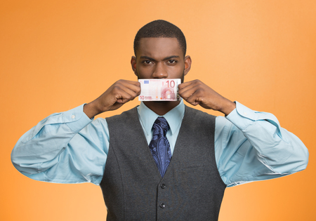 Portrait handsome corrupt guy businessman holding euro bill to mouth silent avoiding truth isolated on orange background.