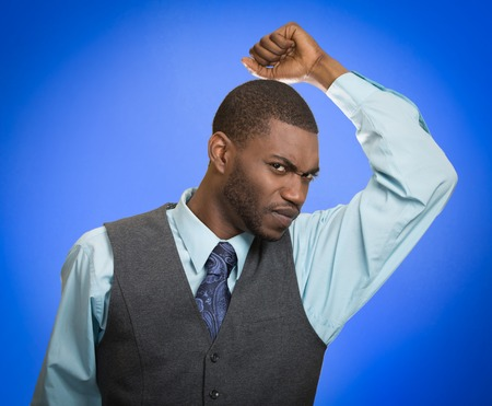 intolerable: Do I stink Young man smelling sniffing his armpit something smells bad foul odor isolated blue background.