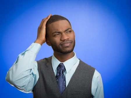 recall: Portrait handsome business man thinking puzzled trying to remember something looking up isolated blue background. Stock Photo