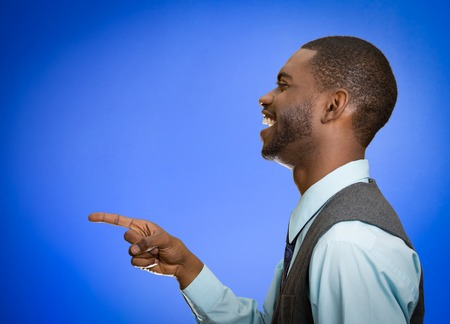 fullness: Closeup side view profile portrait happy young man laughing pointing with finger at someone something isolated blue background.