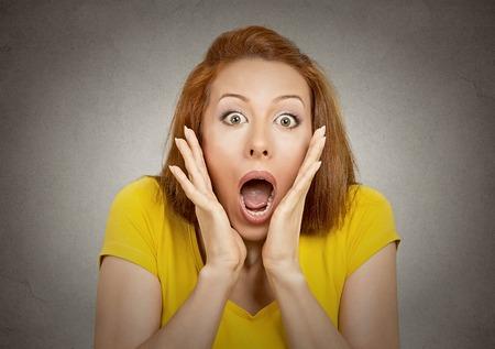 mujer fea: asustada mujer sorprendida mirando a la cámara aislada en el fondo de la pared gris.