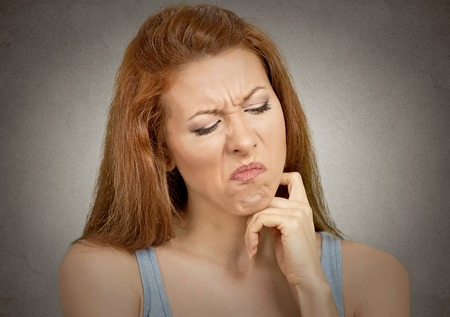 pissed off: Closeup portrait displeased pissed off angry grumpy offended young funny looking woman with bad attitude dissatisfied isolated grey background. Negative human emotion face expression grimace feeling Stock Photo