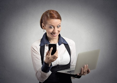 arms trade: Closeup portrait happy shocked surprised business woman corporate executive reading news on smart mobile cell phone holding laptop computer isolated grey background. Human face expression emotion