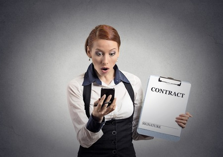 termination: Closeup portrait shocked businesswoman holding contract document looking reading news on smart mobile phone isolated office grey wall background. Human face expression, emotions of corporate executive Stock Photo