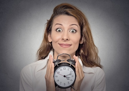 anticipation. Headshot young funny looking excited business woman holding alarm clock waiting isolated grey wall background. Human face expressions, emotions. Time, punctuality, busy schedule concept photo