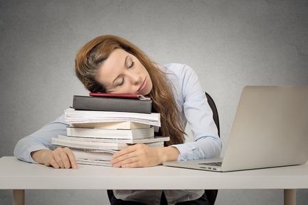 Te veel werk moe vrouw slapen op boeken op haar bureau in de voorkant van de computer geïsoleerd op grijze muur kantoor achtergrond. Drukke schema op de universiteit, op het werk, slaaptekort begrip Stockfoto