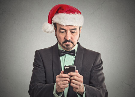 Portrait business man wearing red santa claus hat looking at smartphone searching online holiday season deal sale. Emotion facial expression body language. New technology convenience concept photo