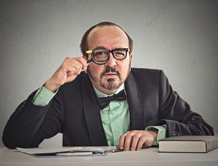 bureaucrat: Curious corporate businessman skeptically looking at you through magnifying glass sitting at desk isolated on office grey wall background. Human face expression, body language, attitude, body language