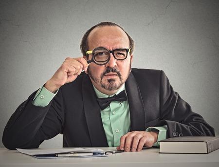 desprecio: Hombre de negocios corporativo curioso escepticismo que le mira a través de la lupa sentado en el escritorio aislado en gris oficina de fondo de la pared. Expresión humano cara, el lenguaje corporal, la actitud, el lenguaje corporal