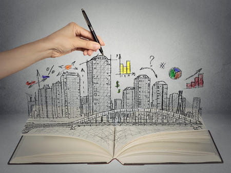hand drawing city skyline business concept growing out of open book on grey wall background. Real estate development, house market economy, investment opportunity photo