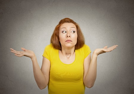 Portrait dumb young woman arms out shrugs shoulders who cares so what I don't know isolated grey wall background. Negative human emotion, facial expression body language life perception attitude Standard-Bild