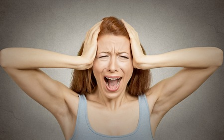 scandal: Closeup portrait stressed woman covers ears with hands yelling screaming with temper tantrum isolated grey wall background. Negative human emotions, facial expressions, feelings reaction attitude