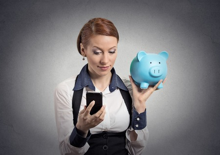 Closeup portrait business woman corporate employee holding piggy bank looking at smart phone isolated grey background. Financial savings, banking concept, customer deal contract agreement satisfaction photo