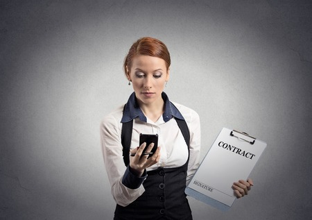 Portrait serious businesswoman signing holding contract document looking at reading news on smart mobile phone isolated grey wall background. Human face expression. Corporate employee executive photo