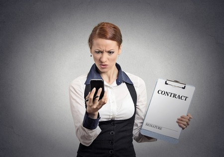 Portrait unhappy skeptical businesswoman holding contract document looking reading news on smart mobile phone isolated office grey wall background. Human face expression emotion of corporate executive photo