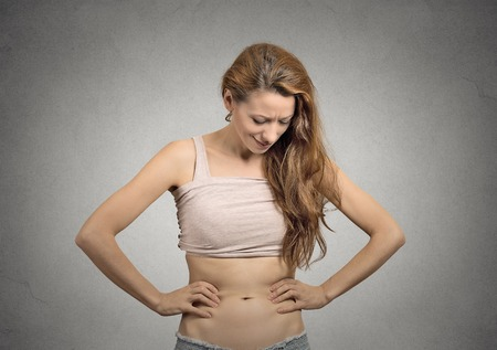 unhappy slim beautiful young girl looks at her abdomen concerned face expression photo