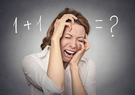 stressed woman cant solve math financial problem isolated on grey wall background. Human face expressions, emotions, feelings photo