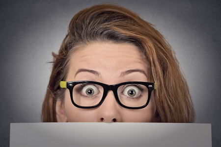 Banner sign woman peeking over edge of blank empty paper billboard. Beautiful young woman with glasses looking surprised and scared funny with wide open eyes isolated on grey wall background photo
