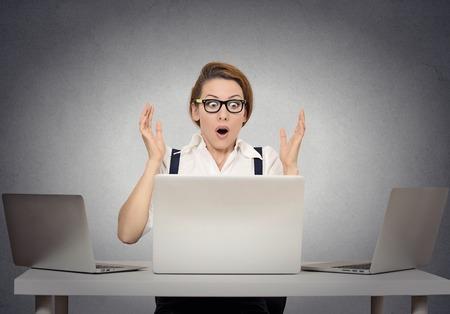 asustadotdo: Empresaria tensionada sorprendió sentado en la mesa en frente de varios equipos en su oficina mirando atónito la boca abierta. Expresiones faciales humanas negativas, las emociones que sienten reacción lenguaje corporal