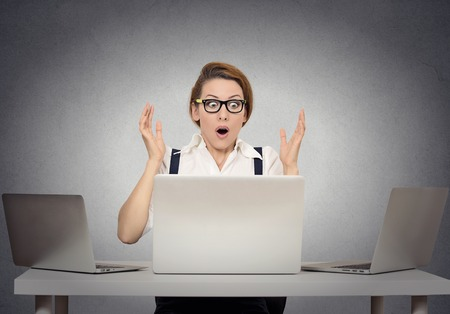 stunned: Stressed shocked businesswoman sitting at table in front of multiple computers in her office looking stunned wide open mouth. Negative human face expressions, emotion feeling body language reaction