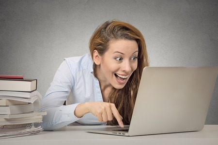 Woman working on computer ready press enter button isolated grey office wall background. Funny funky crazy looking girl excited what she see on laptop screen browsing internet. Face expression emotion Stock Photo