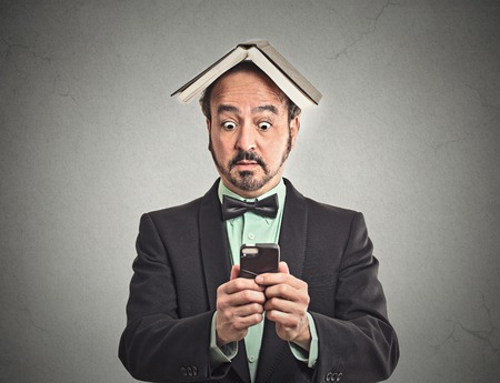 Portrait surprised business man funny looking corporate executive reading news on smart phone holding mobile book over head isolated grey wall background. Human face expression emotion reaction photo