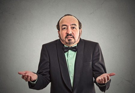 i dont know: Portrait arrogant clueless middle aged business man arms out asking whats problem who cares so what I dont know isolated grey wall background. Negative human emotion facial expression body language
