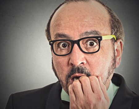business concern: Preoccupied middle aged man. Closeup portrait nerdy guy with glasses biting his nails looking at you craving something anxious isolated grey wall background. Human face expression emotion feeling