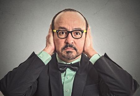 boca cerrada: Retrato del primer medio hombre de negocios de edad con gafas que cubren sus o�dos con las manos cerr� la boca aislado fondo de la pared gris. No escuchen el concepto del mal. La emoci�n humana expresi�n facial percepci�n vida