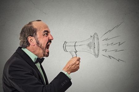灰色の壁の背景に分離したメガホンを持って怒って叫んで男。表情、感情、感情否定的な。宣伝、速報ニュース、電源、ソーシャル メディアの概念