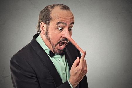 Mann mit langer Nase auf grauem Hintergrund Wand. Lügner Konzept. Menschliche Gesichtsausdrücke, Emotionen, Gefühle.