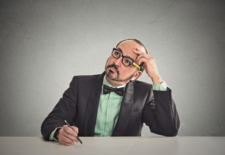bureaucrat: Confused teacher sitting at table scratching his head thinking what idea to write isolated office grey wall background with copy space. Human face expressions, emotions, feelings, body language