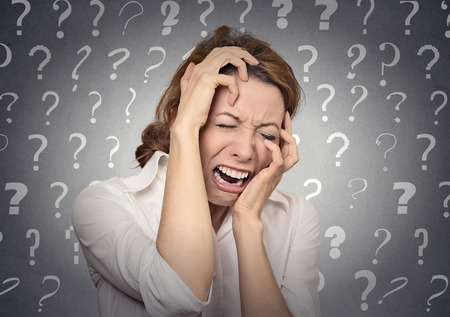 Portrait stressed crying woman has many questions isolated grey wall background with question marks. Human emotion face expression feeling body language life perception problem solution concept photo