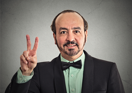 victory symbol: Portrait middle aged businessman smiling with victory hand sign symbol isolated grey wall office background.