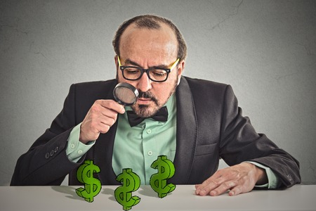 scrooge: Business man looking through magnifying glass at dollar signs symbol on table isolated grey wall office background.