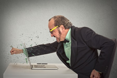 furious businessman throws a punch into computer screaming isolated grey office wall background. photo