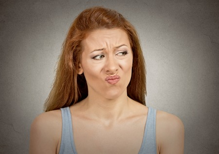 looks: Upset disgusted woman with displeased face expression isolated on grey wall background.