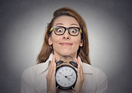 hour glasses: young excited funny looking business woman holding alarm clock isolated grey wall background. Stock Photo