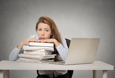 Gedemotiveerd vrouwelijke student vergadering op bureau met een stapel boeken en computer vervelen moe grappig uitziende geïsoleerd op grijze muur schoolbord achtergrond. Stockfoto - 33013352