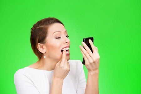 cavity braces: Closeup portrait attractive young woman looking in a mirror checking her teeth isolated on green background