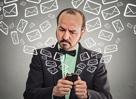 Portrait business man busy sending messages emails from smart phone email icons coming out flying of mobile phone isolated grey wall background.  photo