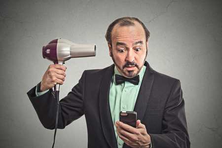 thinning: Closeup portrait business man deal maker reading news on smartphone looking at mobile phone holding hairdryer isolated grey wall background.