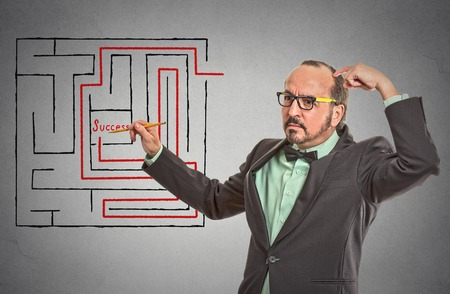 problem solution: man drawing with pencil red path line through labyrinth to achieve get to success isolated grey wall office background.
