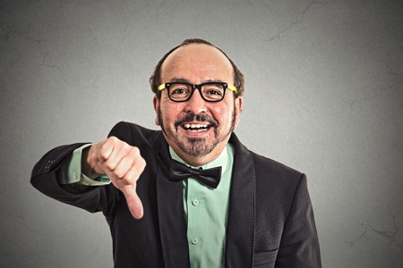 unsatisfied: Closeup portrait sarcastic middle aged man showing thumbs down sign hand gesture happy someone made mistake lost failed isolated grey wall background.
