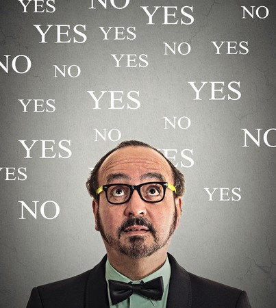 portrait undecided business man looking up grey wall background with yes no choices text. photo