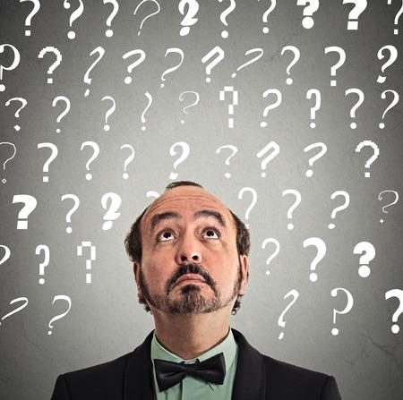toma de decision: hombre de mediana edad con expresi�n de la cara y signos de interrogaci�n perplejos sobre la cabeza mirando hacia arriba aislados fondo gris de la pared.
