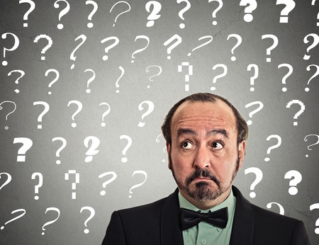 discredit: middle aged man with puzzled face expression and question marks above head looking up isolated grey wall background.