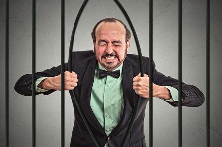 gefangener: Furious starken Geschäftsmann mittleren Alters Biegestäbe seiner Gefängniszelle grauen Wand Hintergrund.