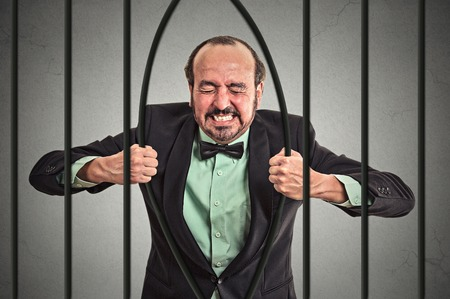 Furious strong middle aged businessman bending bars of his prison cell grey wall background.  Stock Photo
