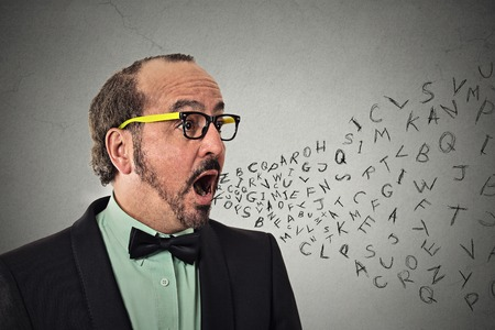 Side view portrait middle aged business man talking with alphabet letters coming out of open mouth isolated grey wall background.
